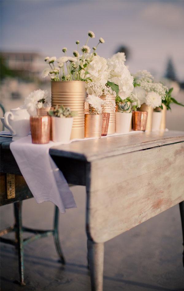 Usa latas de diferentes tamaños y píntalas con pintura metálica para transformarlas en elegantes floreros